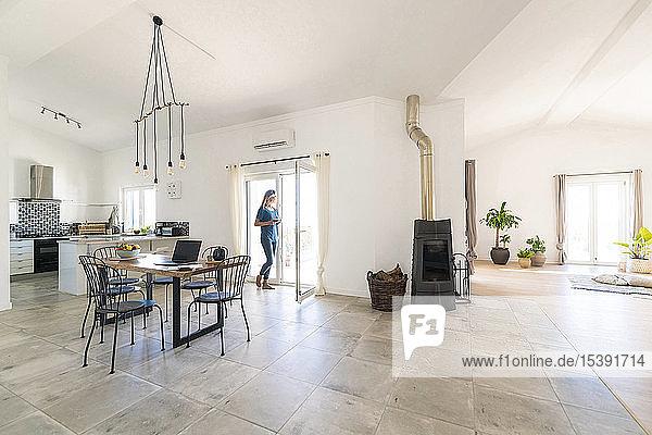Frau steht im Türrahmen eines modernen Wohnzimmers mit Kamin