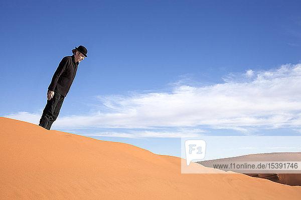 Morocco  Merzouga  Erg Chebbi  man wearing a bowler hat standing crooked on desert dune