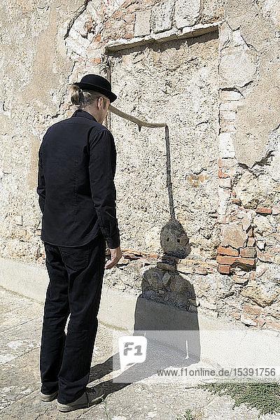 Man wearing a bowler hat balancing a stick at a stone wall