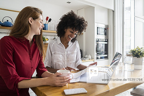 Two women working together in kitchen  using laptop  discussing documents