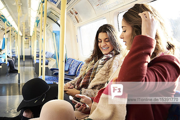 UK  London  two happy women in underground train using cell phone