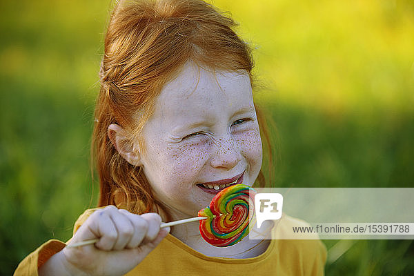 Portrait of happy girl eating a lollipop