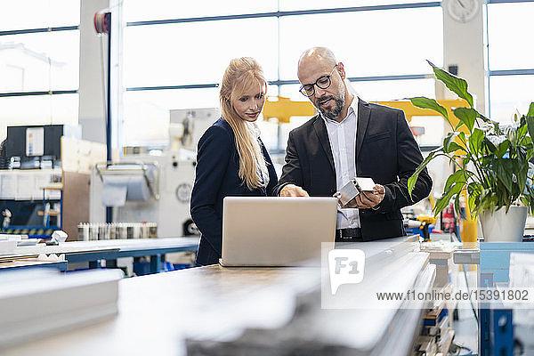 Geschäftsmann und Geschäftsfrau mit Laptop und Werkstück im Gespräch in der Fabrik