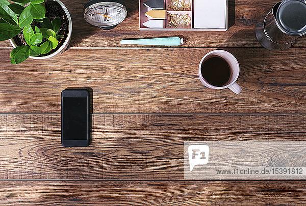 Hölzerner Büroschreibtisch mit Smartphone und Kaffeetasse  Draufsicht