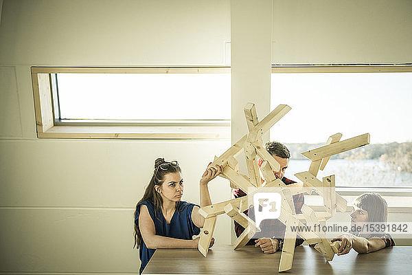 Gruppe von Kreativen  die ein Holzobjekt für ein Projekt bauen