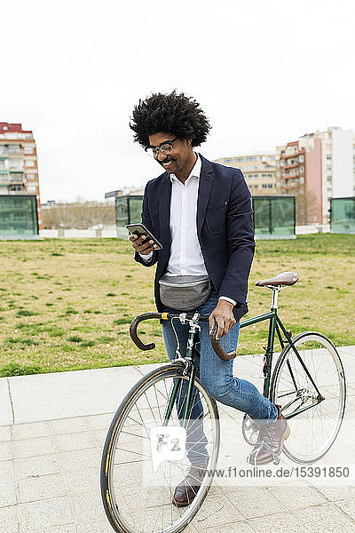 Spain  Barcelona  smiling businessman on bicycle using cell phone in the city