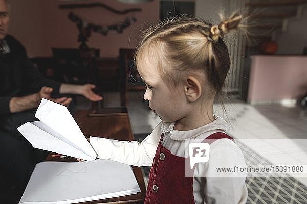 Mädchen hält Papierflieger im Wohnzimmer mit Großvater im Hintergrund