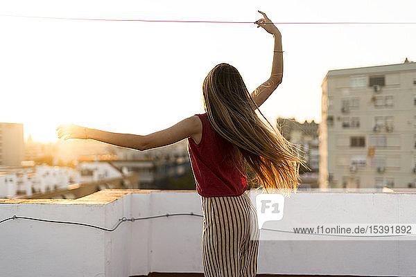 Rückansicht eines anmutigen Teenager-Mädchens  das sich bei Sonnenuntergang auf der Dachterrasse der Stadt bewegt