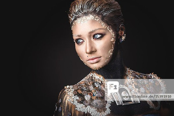 Portrait of a blue eyed young girl with creative golden makeup in the style of icon painting isolated on black background.