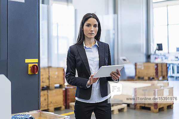 Porträt einer Geschäftsfrau mit Tablette in einer Fabrik