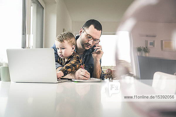 Busy father working at table in home office with son sitting on his lap