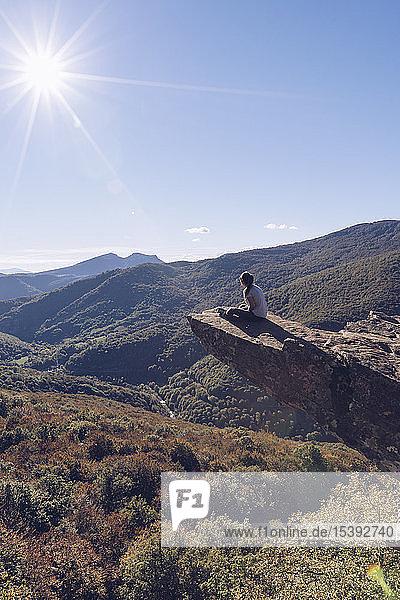 Spanien  Navarra  Wald von Irati  Frau sitzt auf einem Felssporn über einer Waldlandschaft im Gegenlicht