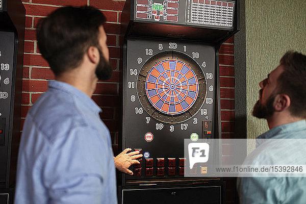 Two men playing darts setting electronic dartboard