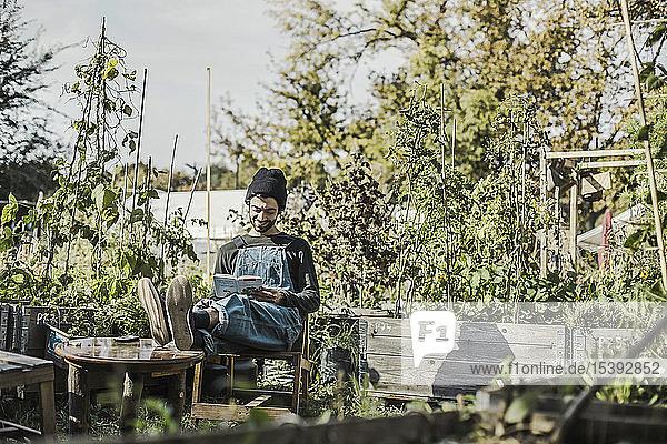 Smiling man reading book in urban garden