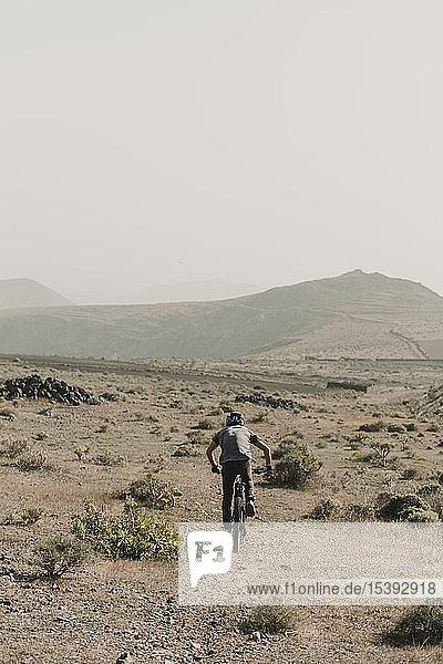Spanien  Lanzarote  Mountainbiker auf einem Ausflug in die Wüstenlandschaft