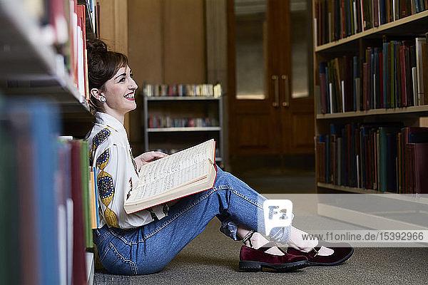Studentin liest Buch in einer öffentlichen Bibliothek