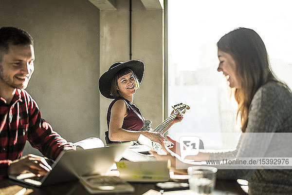 Creative professionals working toghether in oficem  woman with hat paying the guitar