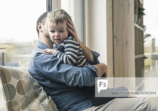 Vater kuschelt mit Sohn zu Hause