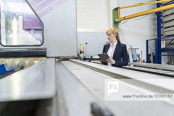Geschäftsfrau mit Tablette am Fließband in der Fabrik