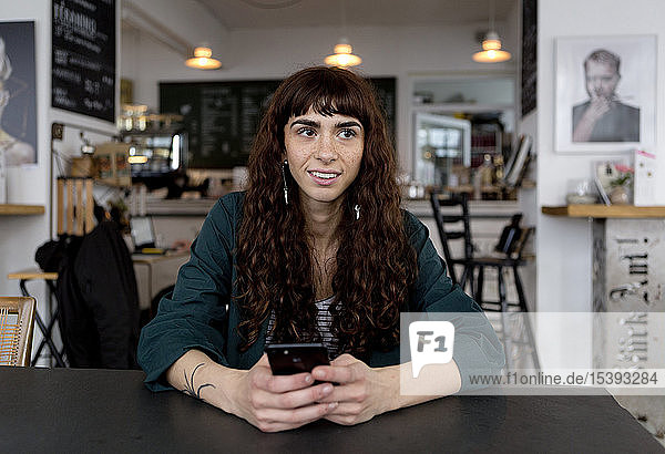 Smiling young woman with cell phone in a cafe looking around