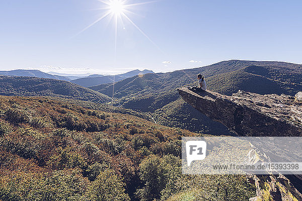 Spain  Navarra  Irati Forest  woman sitting on rock spur above forest landscape in backlight
