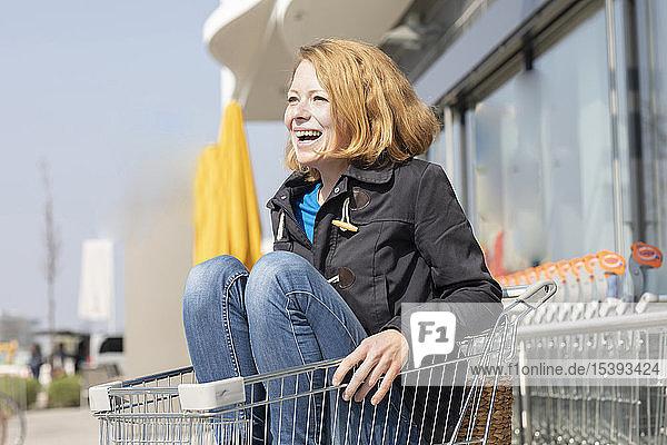 Porträt einer lachenden Frau  die in einem Einkaufswagen vor einem Supermarkt sitzt