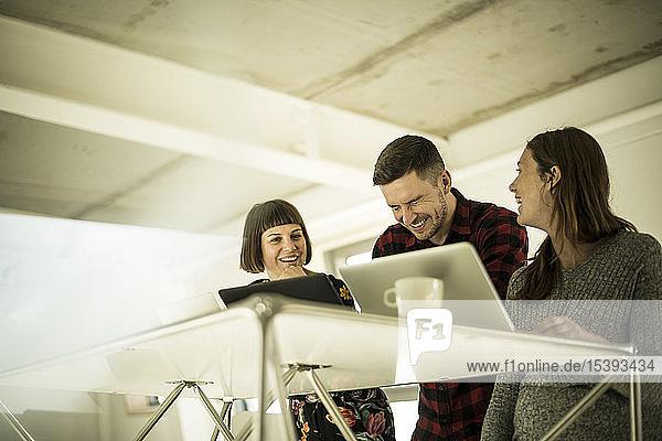 Kollegen sitzen im Büro  arbeiten zusammen  haben Spaß