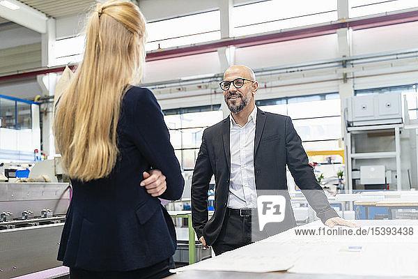 Lächelnder Geschäftsmann und Geschäftsfrau mit Plan auf dem Tisch in der Fabrik