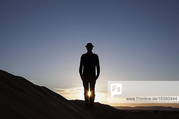 Morocco  Merzouga  Erg Chebbi  silhouette of man wearing a bowler hat standing on desert dune at sunset