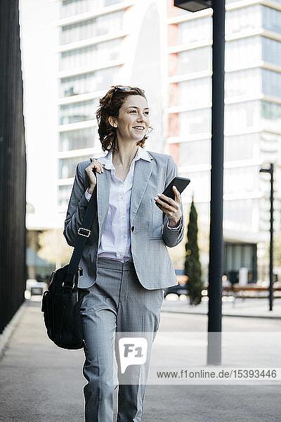 Geschäftsfrau mit Smartphone  die in der Stadt pendelt