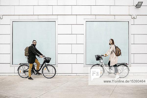 Porträt eines Mannes und einer Frau mit E-Fahrrädern an einem Gebäude stehend