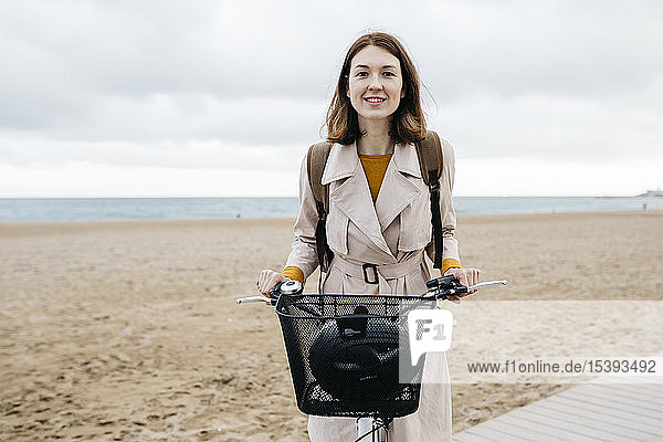 Portrait of smiling woman with e-bike at the beach