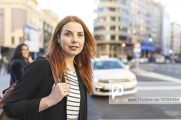 Porträt einer rothaarigen jungen Frau mit Nasenpiercing in der Stadt