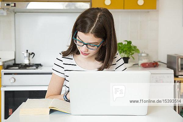 Mädchen benutzt Laptop und schaut sich in der Küche ein Buch an