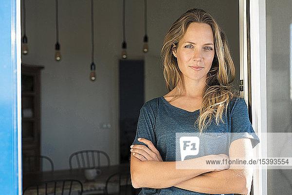 Porträt einer selbstbewussten Frau  die sich zu Hause am offenen Fenster lehnt