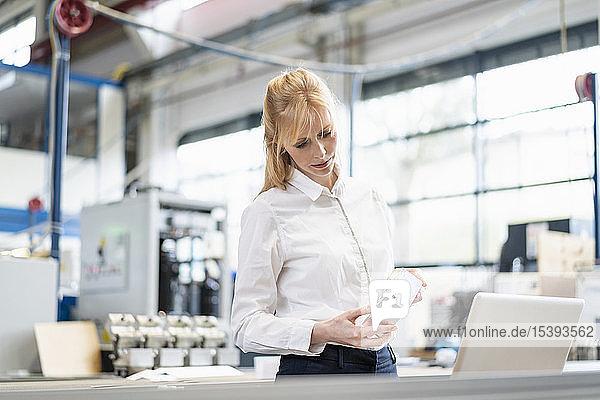 Geschäftsfrau mit Laptop untersucht Werkstück in Fabrik