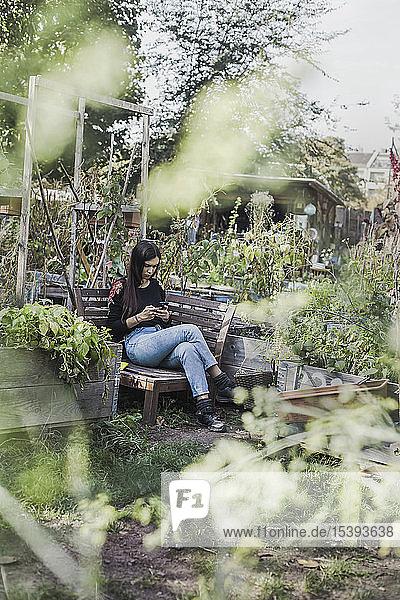 Frau benutzt Smartphone im Stadtgarten