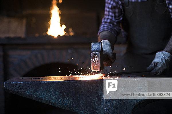 Nahaufnahme eines Schmiedes bei der Arbeit mit dem Hammer am Amboss in seiner Werkstatt