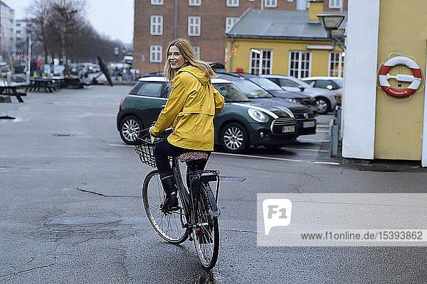 Dänemark  Kopenhagen  glückliche Frau fährt bei Regenwetter Fahrrad auf der Uferpromenade