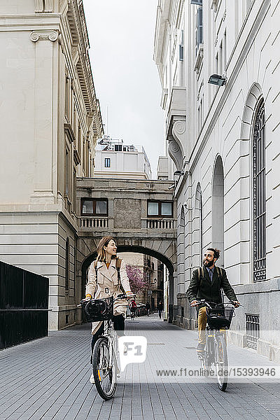 Smiling couple riding e-bikes in the city