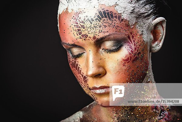 Portrait of Beautiful Young Woman with creative fantasy bird makeup.