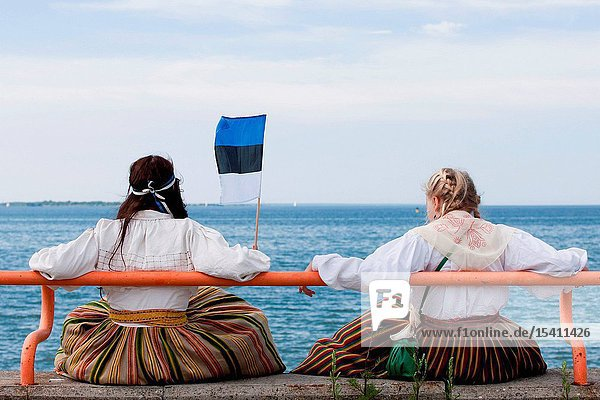 Girls in national costumes sitting by the sea