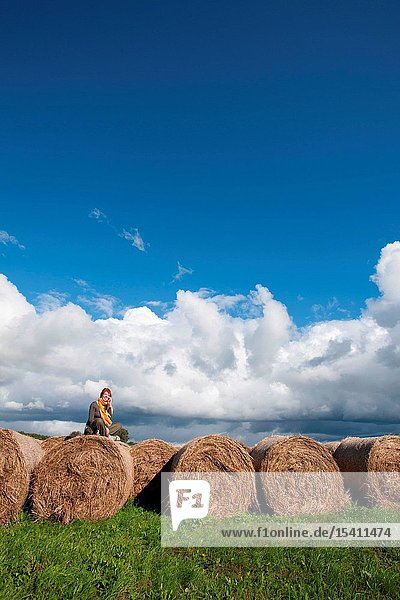 A woman talking on the phone on a field with bales of hay
