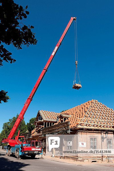 Crane lifting roof tiles on a building