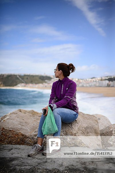 Young woman watches the sea from the dock of Nazare  Portugal.