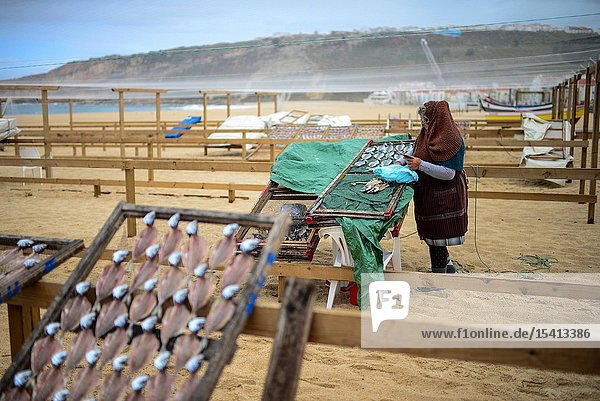Elderly woman sells dry fish on the beach of Nazare  Portugal.