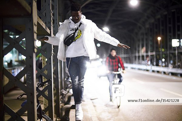 Young man balancing on metal construction of bridge Hackerbrücke  Hacker bridge  at night in city  next to street  bicycle driver  in Munich  Germany