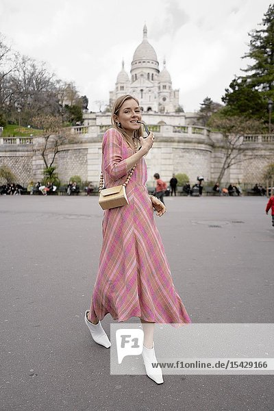 Stylish blogger woman in front of touristic sight Basilica Sacré-Cœur  during fashion week  in city Paris  France  in city Paris  France