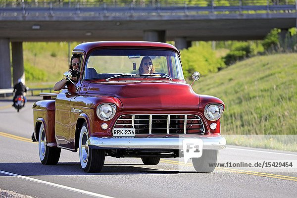 Salo  Finland. May 18  2019. Woman drives a mid-1950s Chevy pickup  the man on passengers seat is photographing on Salon Maisema Cruising 2019. Credit: Taina Sohlman/agefotostock