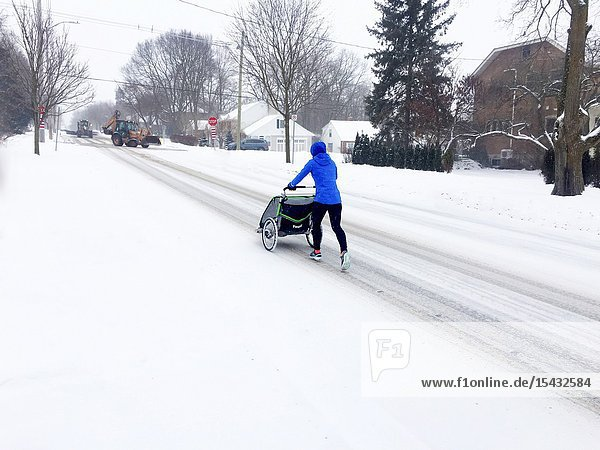 A woman pushes a baby carriage on a snow covered street  Canada.